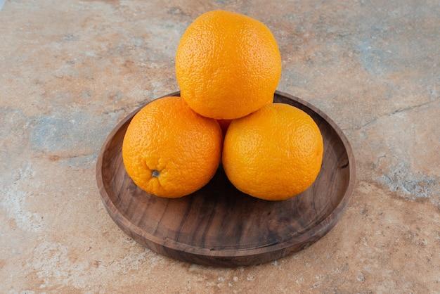 Arance acide fresche sul piatto di legno.