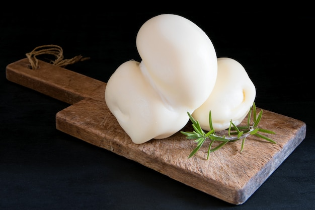 Fresh southern italian traditional scamorza semi-soft cow cheese on a cutting board on a black table, ready to eat, close up