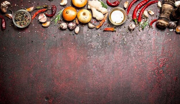 フレッシュスパイス。唐辛子と玉ねぎを使ったさまざまな香辛料。素朴な背景に。