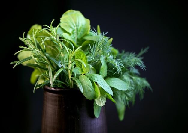 Свежие пряные травы - мята, розмарин, укроп, руккола и шпинат в черной чашке на черной поверхности
