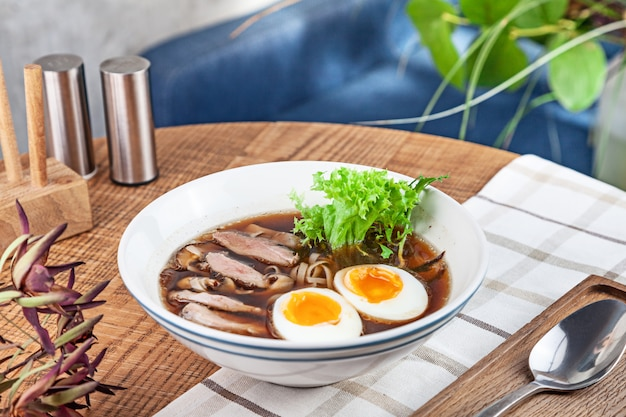 Fresh spicy soup with duck, egg, mushrooms and noodle. traditional vietnamese noodle soup in bowl. asian/vietnamese cuisine. copy space for design. served lunch in restaurant. close up