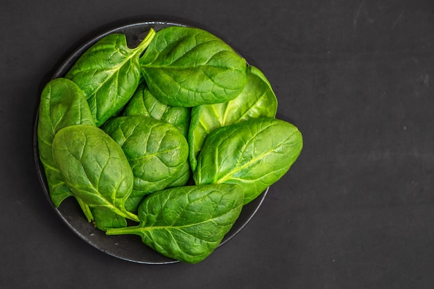 Fresh spinach leaves in bowl on dark. top view.