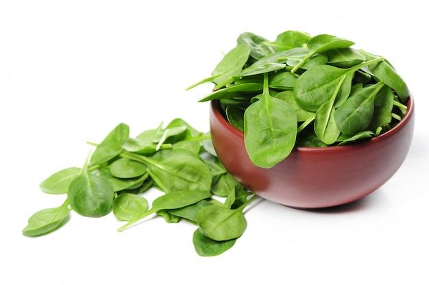 Fogli freschi degli spinaci in ciotola isolata