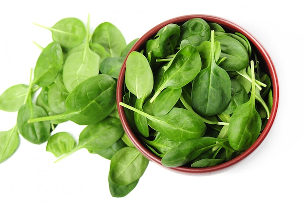 Fresh spinach leaves in bowl isolated
