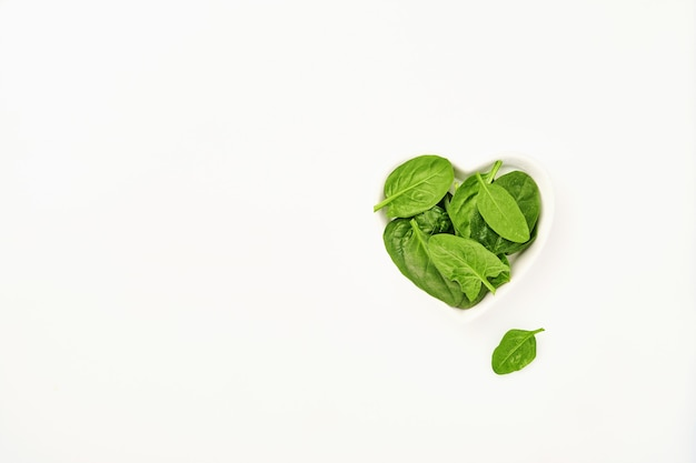 Fresh spinach leaves in bowl of the shape of heart on white, isolated.