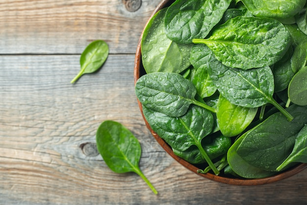 Fresh spinach leaves in bowl on wooden table.