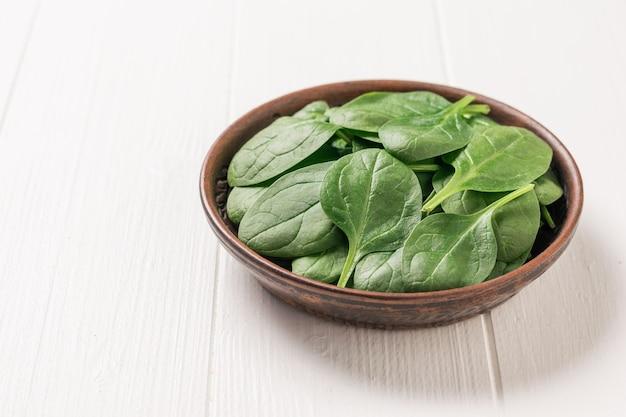신선한 시금치는 흰색 소박한 테이블에 있는 점토 그릇에 나뭇잎. 건강을 위한 음식. 채식주의 자 음식. 정상에서 본 모습.