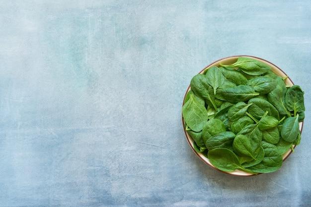 Свежие листья шпината на белой тарелке. здоровая веганская еда. вид сверху, копировать пространство