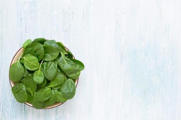 青いテーブルの白いプレートに新鮮なほうれん草の葉。健康的なビーガンフード。上面図、コピースペース。