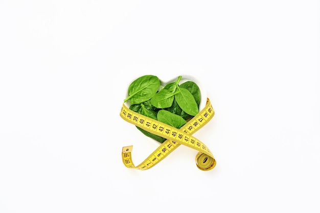 Fresh spinach leaves with measuring tape in bowl of the shape of heart on white, isolated.