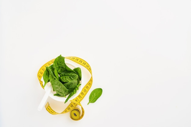 Fresh spinach leaves with measuring tape in white cocktail glass on white, isolated.