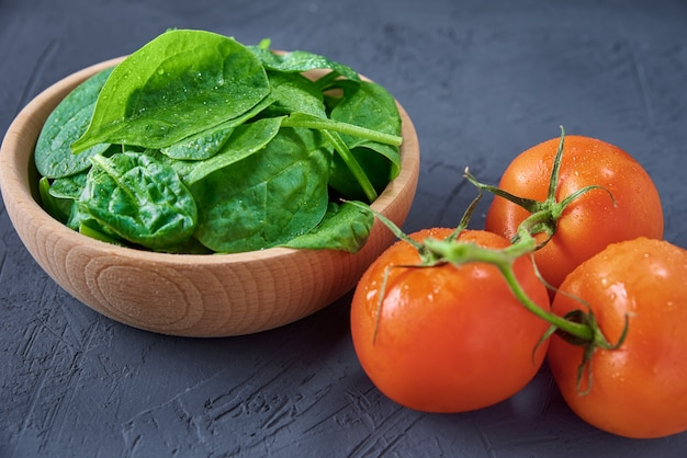 Fresh spinach leaves in wooden bowl and tomato on a dark background.