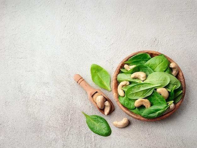 Салд из свежего шпината с орехами кешью в деревянной тарелке на бетонных столах.
