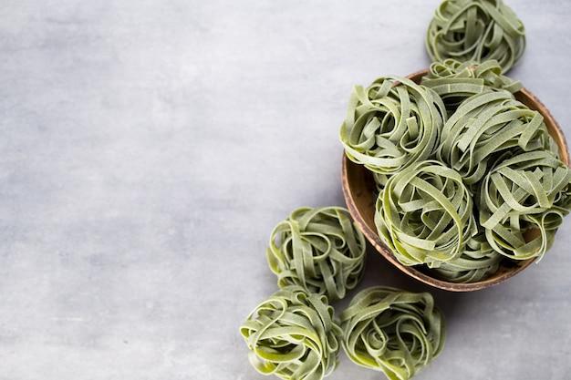 Свежий шпинат с зеленой пастой на сером.