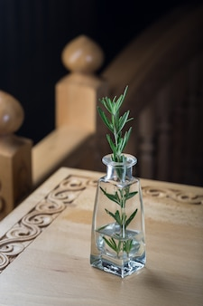 Свежая веточка розмарина в прозрачной бутылке с водой, стоящей на резном деревянном столе.