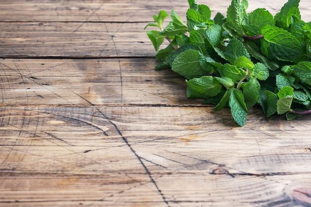 コピースペースと木製の背景に香りのよいミントの新鮮な小枝。