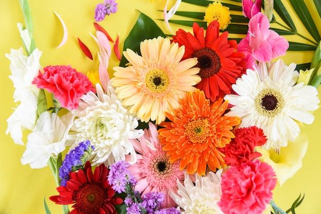 Свежие весенние цветы обрамляют тропическое растение герберы, хризантемы, разноцветные цветы, разнообразные и зеленые листья