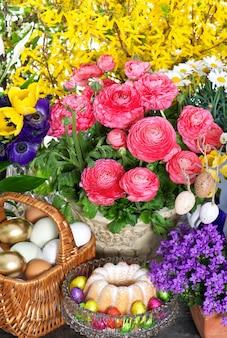 Fresh spring flowers with easter cake eggs decoration ranunculus campanula forsythia tulips