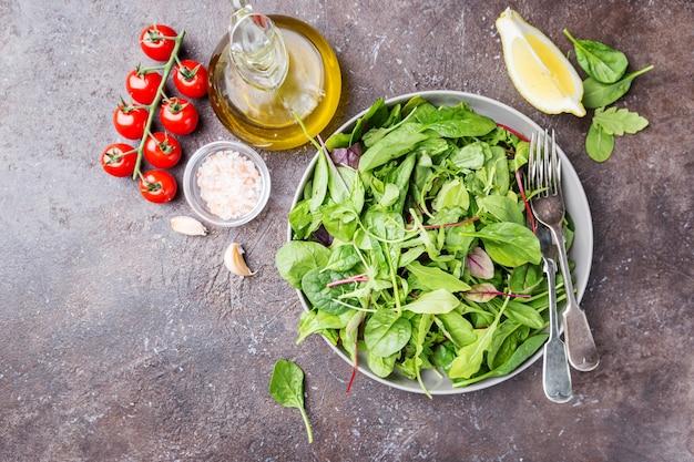ほうれん草、ルッコラ、ロメインレタス、レタスを混ぜ合わせた新鮮な春のグリーンサラダを暗闇の中で皿に盛り付けます