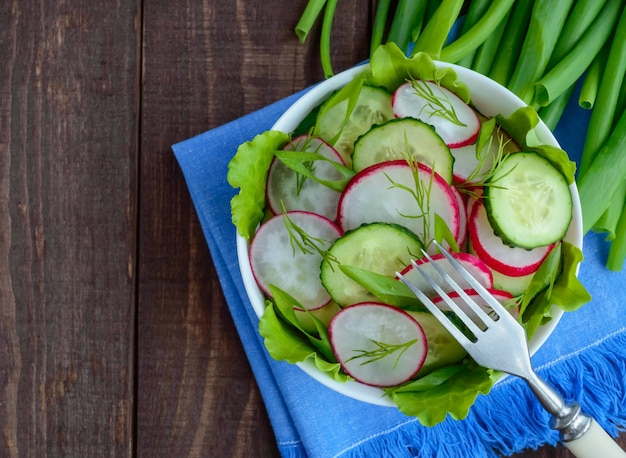 오이, 무, 나무 바탕에 파란색 냅킨에 녹색 신선한 봄 빛 채식 샐러드. 상위 뷰.