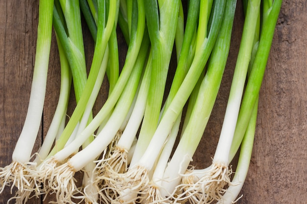 Fresh spring onion or scallions on wood plank in top view flat lay prepare for cooking.