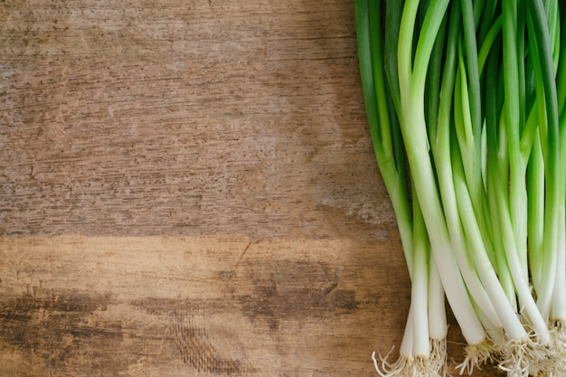 Fresh spring onion or scallions on wooden plank