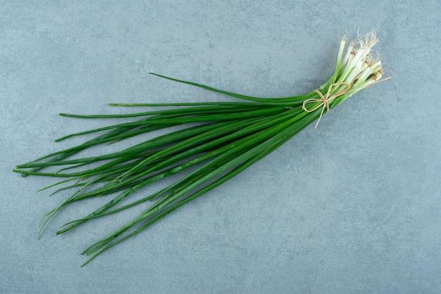Свежий зеленый лук на мраморе.