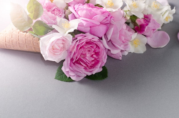 Fresh spring roses in waffle cone. beautiful romantic background in flat lay style.