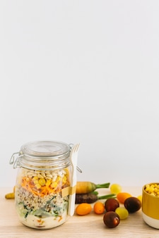 Fresh spring salad in closed jar with white fork and vegetables on wooden table