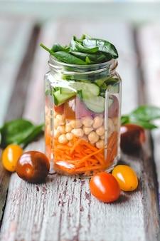 にんじん、ひよこ豆、トマト、きゅうり、ほうれん草の新鮮な春のサラダをガラスの瓶に入れておやつに。家族全員のための健康的な適切な栄養の概念。セレクティブフォーカス