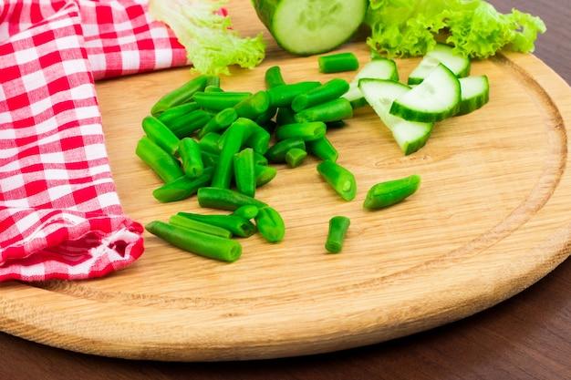Свежий весенний салат с огурцом, салатом и зеленым горошком на деревянной доске с пространством для свободного текста.