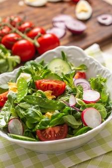 Свежий весенний салат с зелеными листьями томаты яичный редис красный лук молодой горошек сыр прошутто фета и оливковое масло.