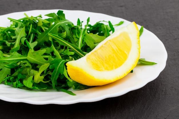 Свежий весенний салат с рукколой и лимоном, в миске на темном каменном фоне с пространством для свободного текста.