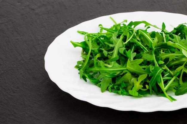 Свежий весенний салат с рукколой, в миске на темном каменном фоне с пространством для свободного текста.