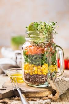メイソンジャーにサーモン、キノア、ルッコラ、クレスサラダ、コーンを入れた新鮮な春のサラダ。