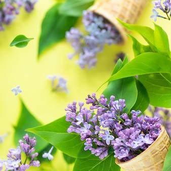 飛行中のアイスクリームのウェーハカップを飛んでいるライラックの花の新鮮な春のテクスチャ。春の開花コンセプト