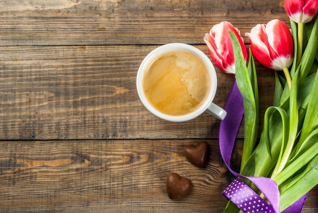 Fresh spring tulips flowers with chocolate hearts candy and coffee mug