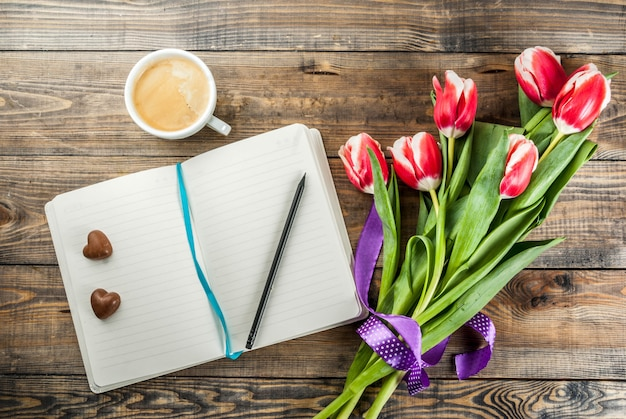 Fresh spring tulips flowers with notepad, chocolate hearts candy and coffee mug