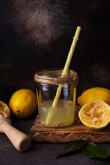 ガラスの瓶にジューサーを入れたレモン半分からの絞りたてのジュース、セレクティブフォーカス