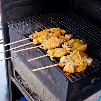 Fresh squid barbeque grilled on charcoal stove