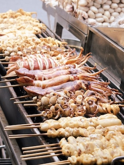 Fresh squid on skewers and grilled over charcoal. sea food ready to eat.