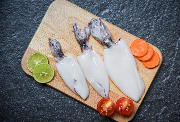 Fresh squid on wooden cutting board top view