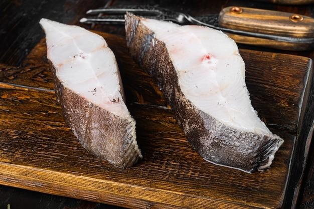 古い暗い木製のテーブルの背景に、食材とローズマリーのハーブと新鮮なステーキ生魚のオヒョウセット