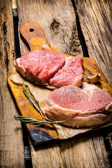 Fresh steaks on an old wooden board on wooden background