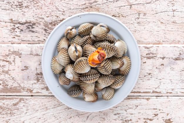 Свежие приготовленные на пару ракушки, вареные ракушки в керамической тарелке на фоне старой белой деревянной текстуры, вид сверху, легкая и воздушная фотография еды, кровяная ракушка