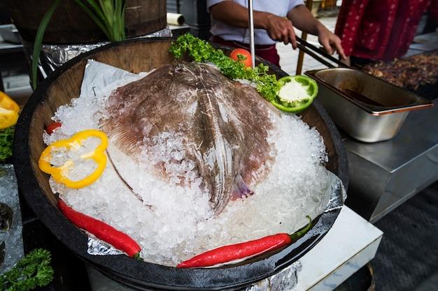新鮮なアカエイの魚が市場で売られています。氷の樽の中の大きな新鮮なスティングレイがレストランにあります