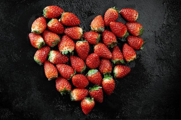 Форма сердца массива свежей клубники на черной предпосылке. концепция любви. концепция дня святого валентина. зимняя концепция.