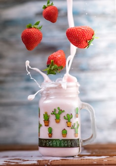 Fresh strawberries falling into a glass to make a delicious strawberry smoothie. wood wall