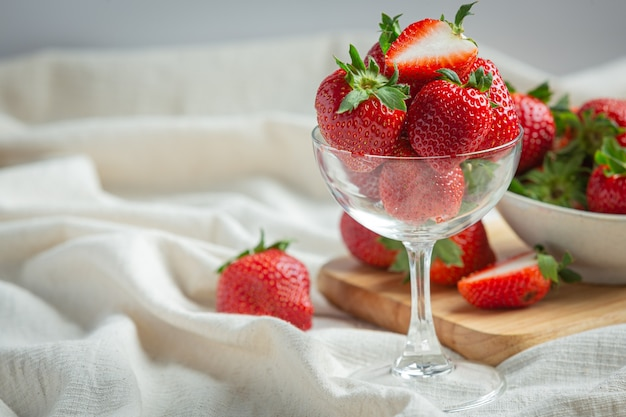 Fresh strawberries in glass on wooden table