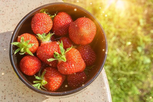 花崗岩のテーブルの上の黒いプレートに、日光に照らされた新鮮なイチゴ。